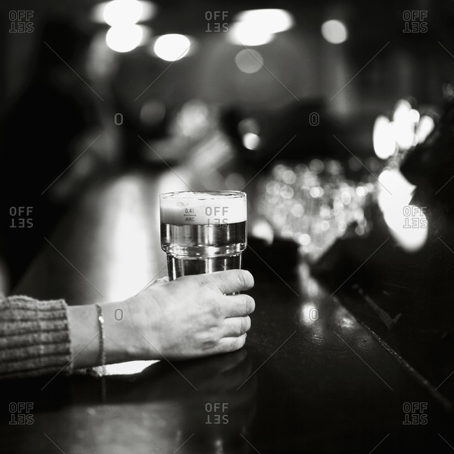 Woman holding a glass of beer in bar