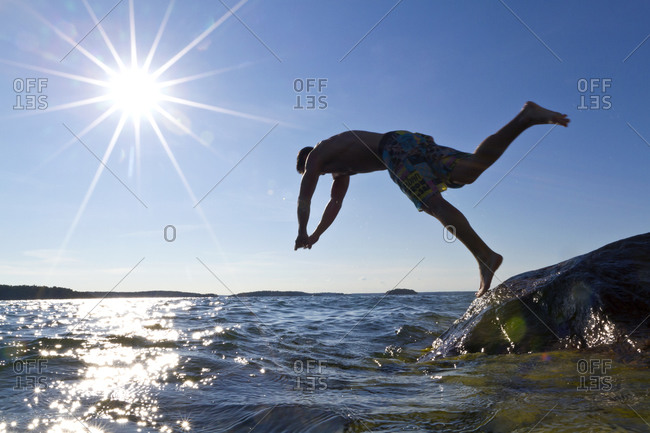 Young man jumping into the sea from a rock