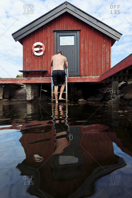 Man climbing up on a swim ladder at a boat house