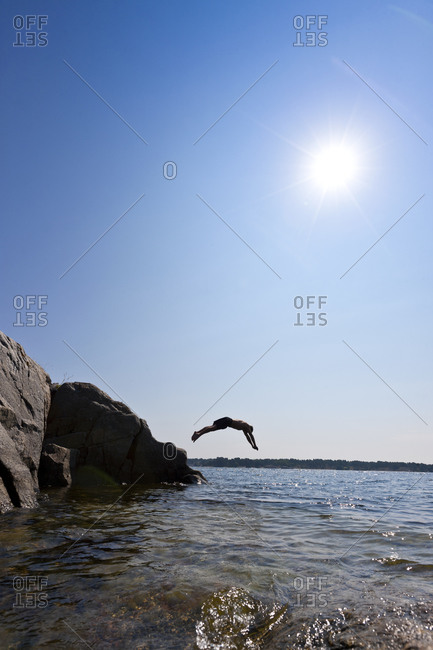 Man jumping from cliff into the sea