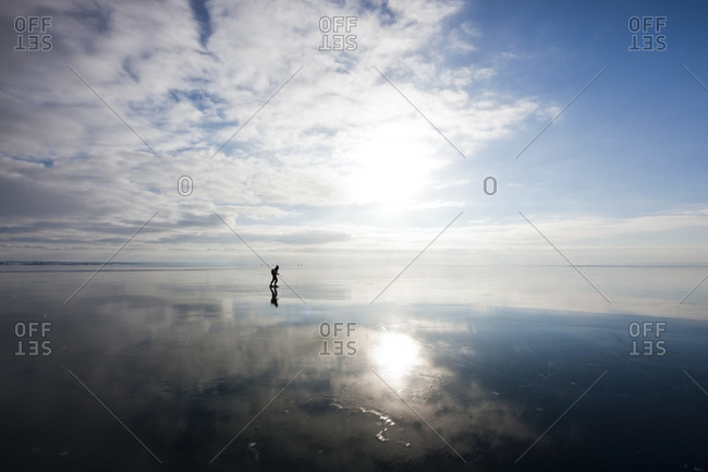 Man ice-skating on a frozen lake