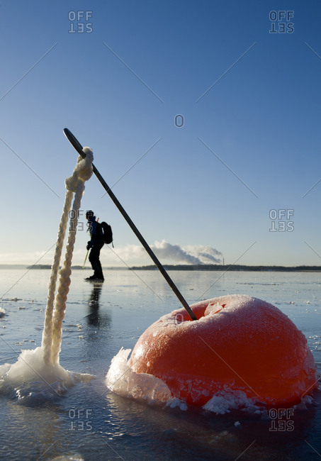 Skater at a buoy on a frozen lake