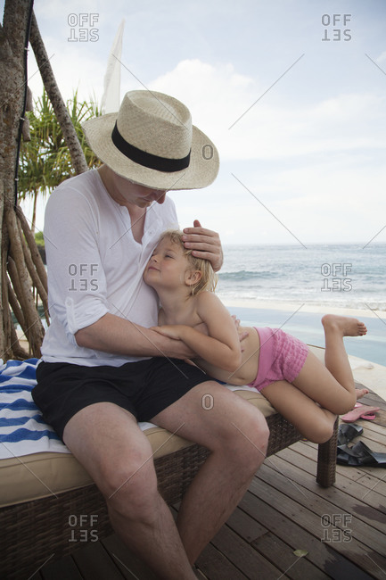 Father and daughter relaxing on a beach