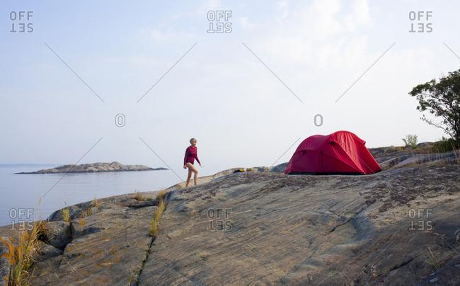 Woman camping on a seashore
