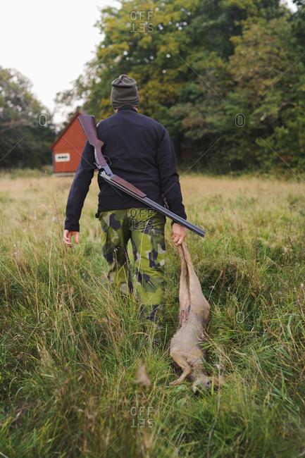 Hunter dragging a deer through a field