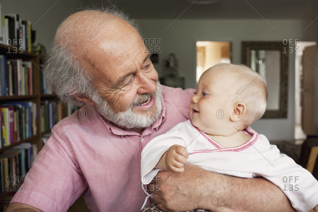 Elderly man holding a baby