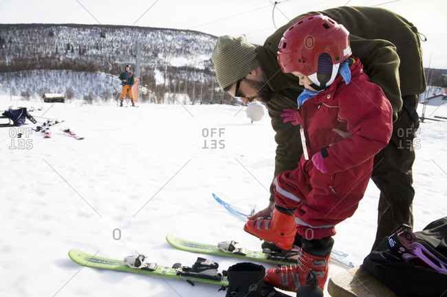 Man helping his daughter to put on the skis