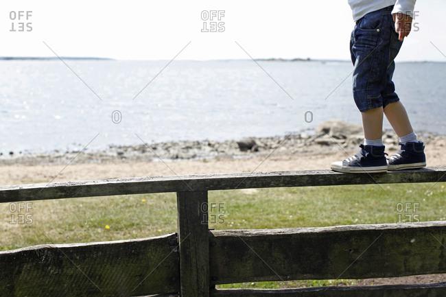 Boy balancing on a fence