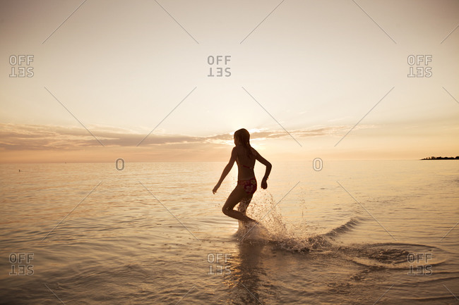 Young girl running into the ocean