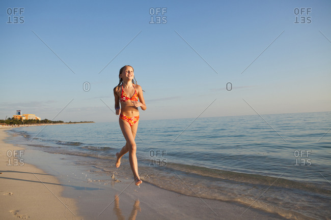 Young girl running on a sandy beach