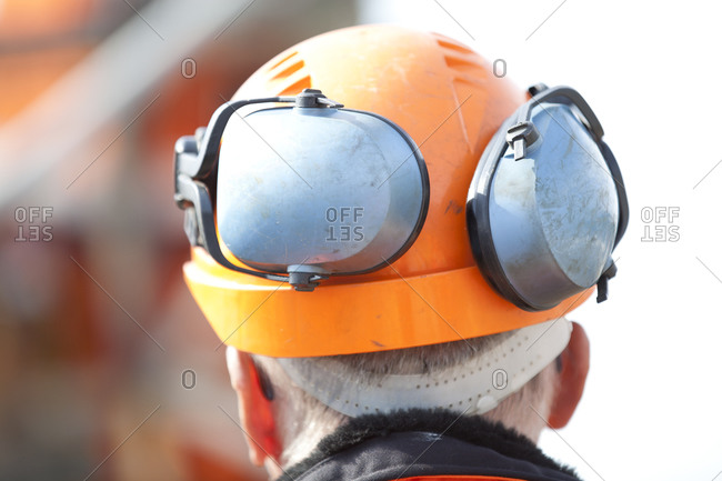Worker wearing hardhat and ear protectors