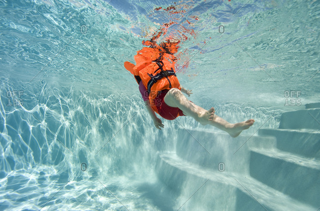 Child in life vest in a swimming pool
