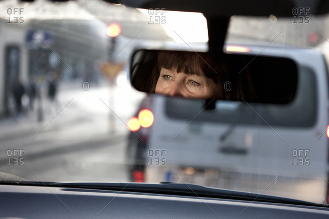 Woman reflecting in rear view mirror