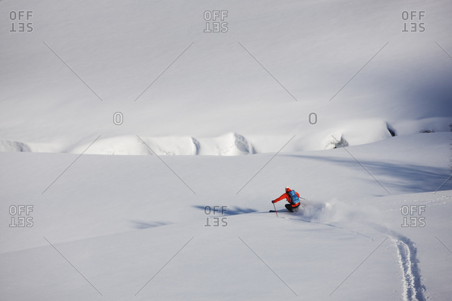 Man downhill skiing on a snowy slope