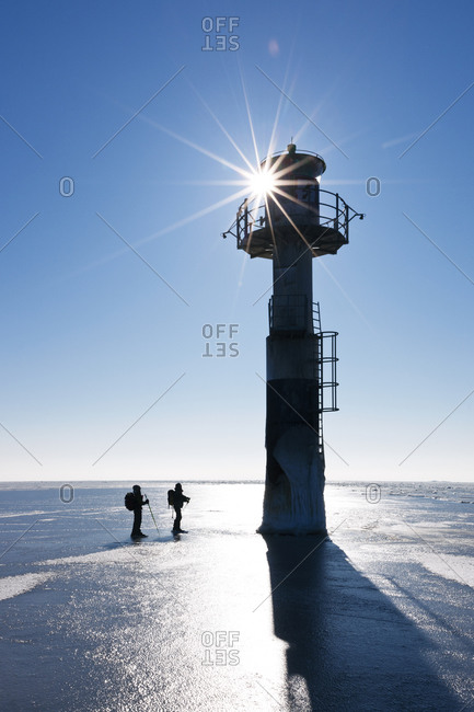 People ice skating at a lighthouse