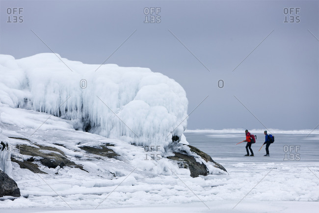 Couple ice-skating on a frozen coast