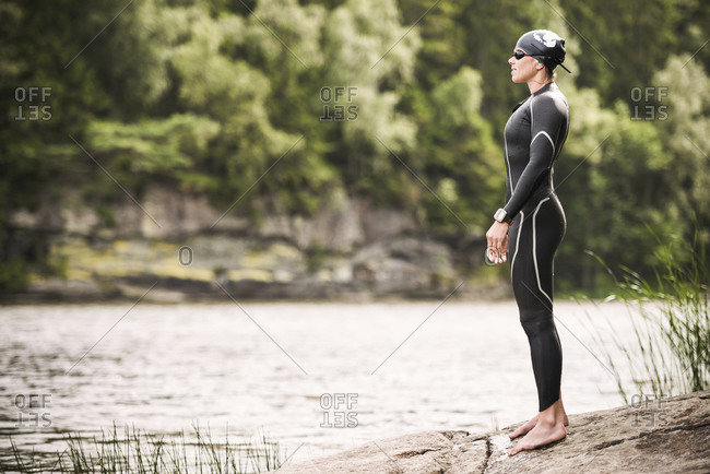 Woman in wetsuit standing on the shore