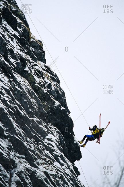 A man mountain climbing with skis on his back