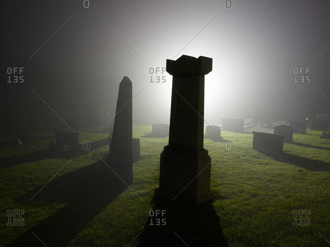 Misty graveyard at night