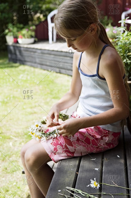 A girl tying a wreath of flowers