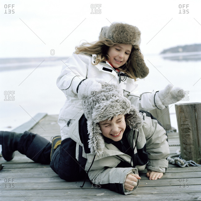 Two children playing on a jetty