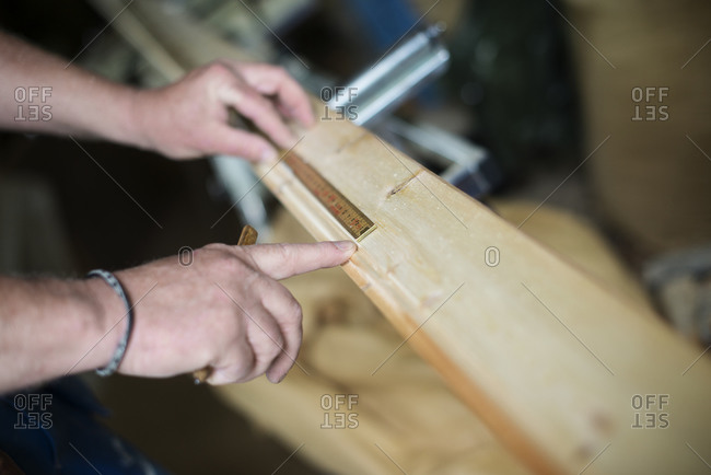 Man measuring a wooden plank