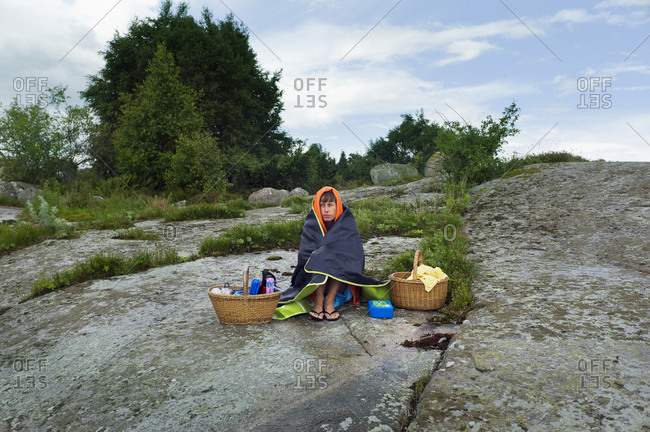 Woman sitting on rock with baskets