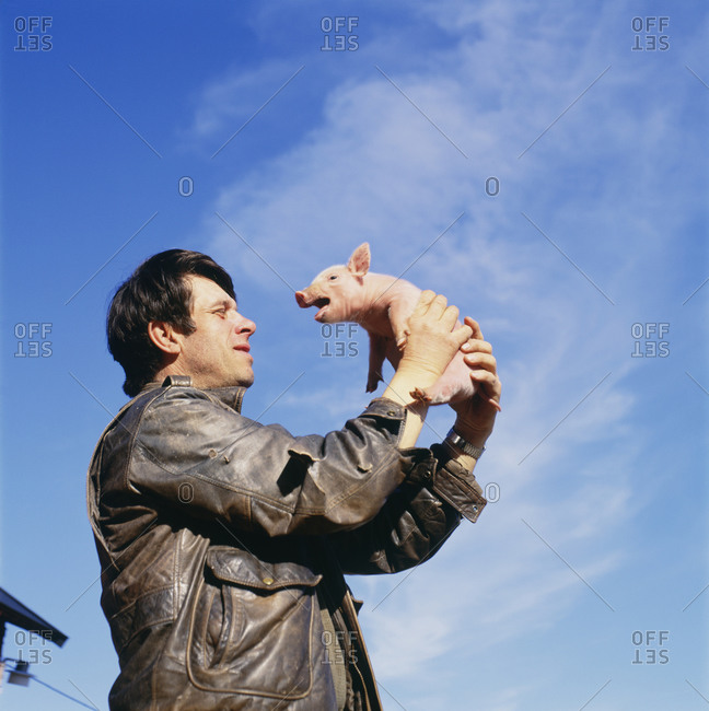 Man holding piglet in hands