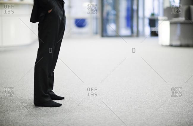 Businessman standing in socks in an office