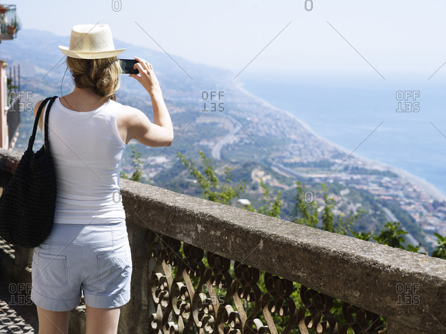 Woman taking pictures of an Italian coastline