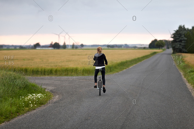 Girl on unicycle on a country road