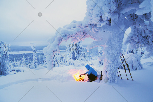 Woman boiling water at a campfire in winter