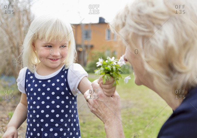 Young girl giving flowers to her grandmother