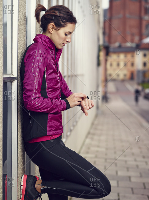 Young woman checking the time on her morning run