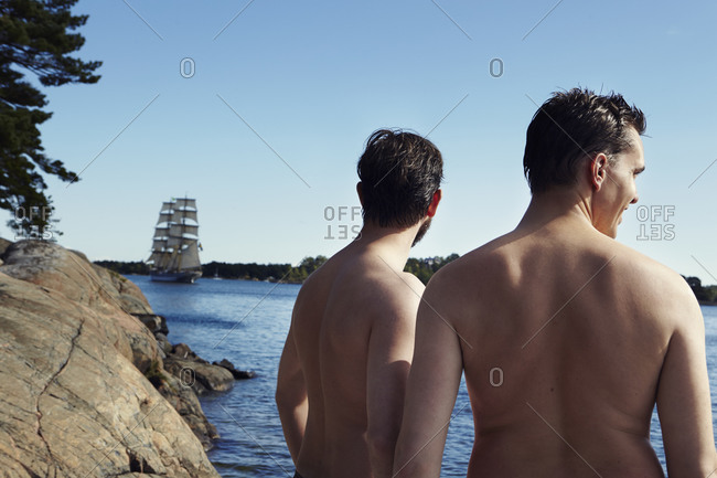 Two young men looking at a sailing boat in Sweden
