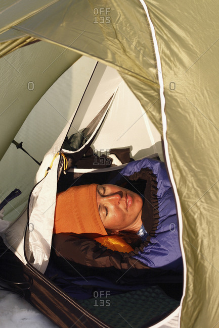 Young woman sleeping in a tent in Lapland, Sweden