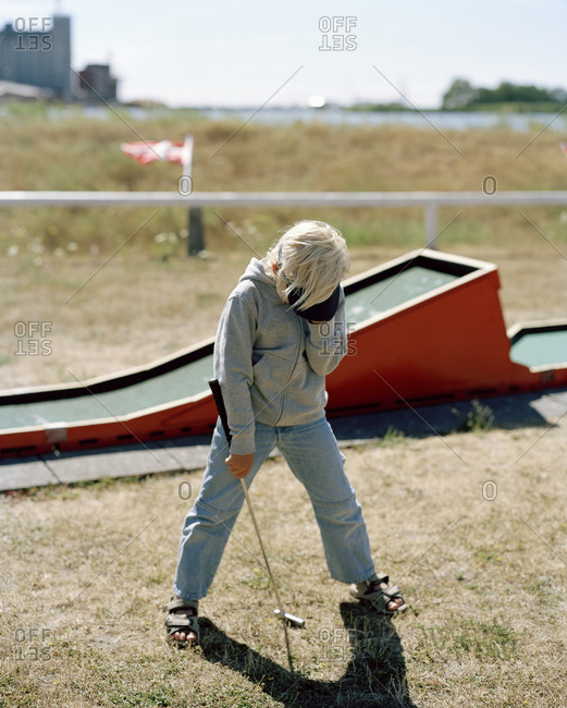 A boy playing mini golf