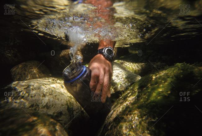 Underwater of person filling water bottle in stream