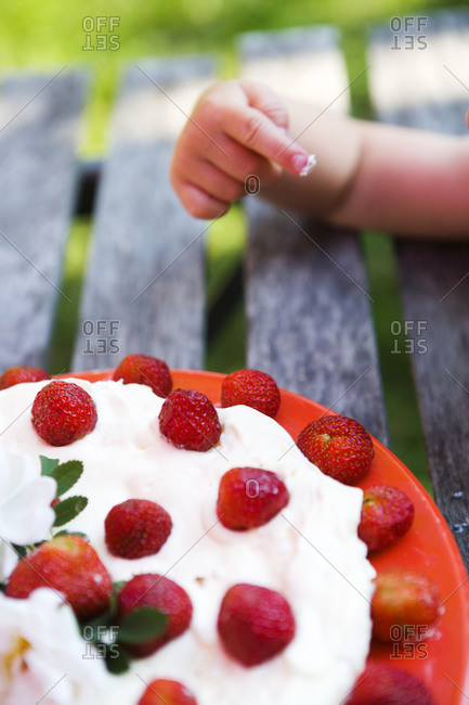 Child tasting a strawberry cake