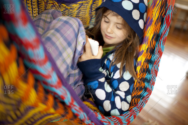 Young girl in hammock indoors plays with smartphone