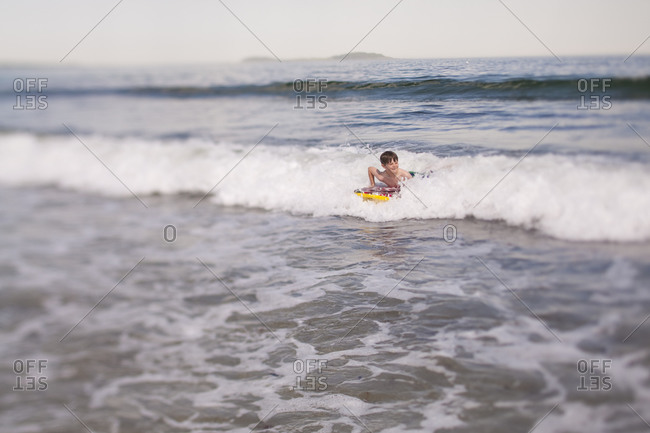 Boy body boarding at Scarborough Beach in Maine