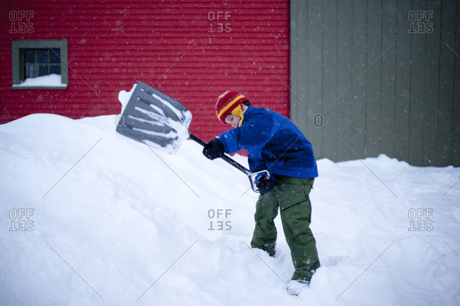 Boy shovels snow at his home in Maine