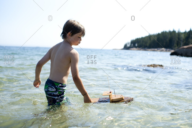 Young boy playing with toy boat in ocean