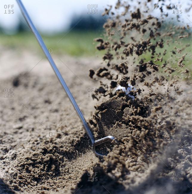 A golf club swinging in a sand trap