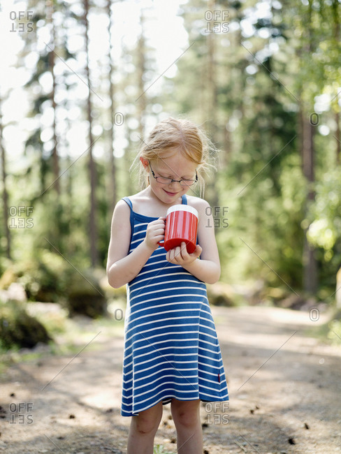 A girl with a mug in the forest
