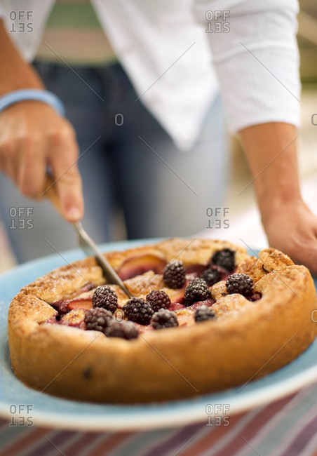 A mulberry pie being cut