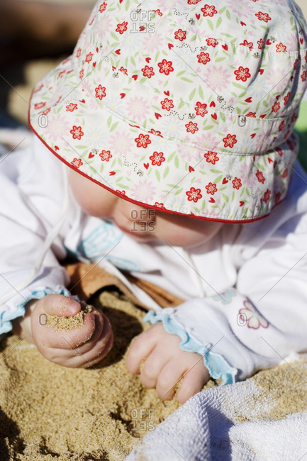 A baby digging in sand
