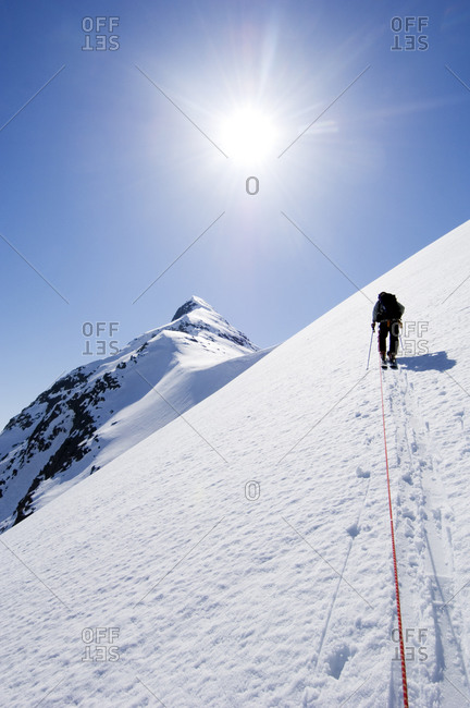 A skier climbing up a steep mountain side