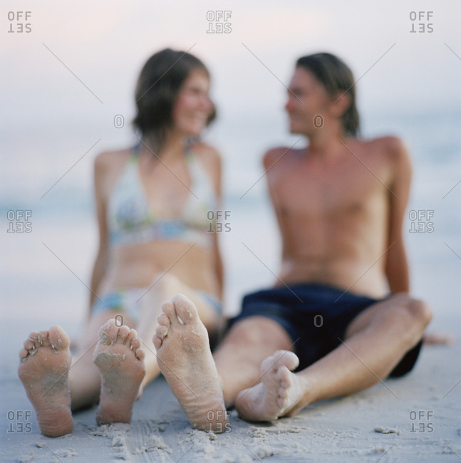 Young couple sitting on the beach in Thailand