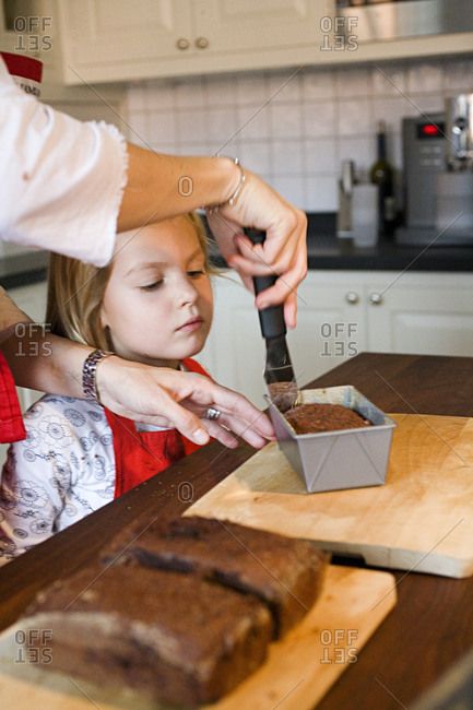 A girl baking cake with mother